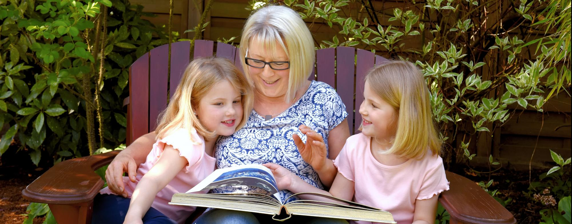 Image of Grandparent with two grandchildren looking at a book